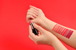 canvas print picture - Lipstick swatches on woman hand isolated on red background.