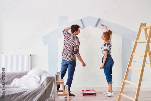 Photo Young couple painting the interior wall in their new apartment