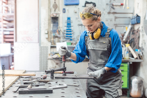 Fotomural Female mechanic working with clamp and spanner on workpiece