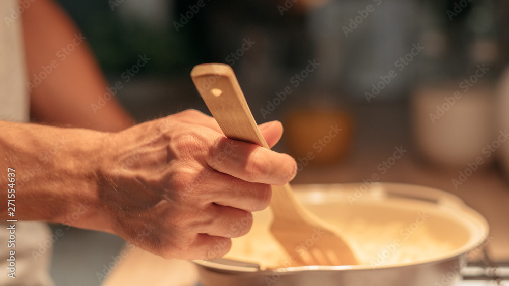 Fototapety, obrazy: Cooking hobby and leisure. Traditional culinary recipe. Closeup of man hand using spatula during preparing meal.