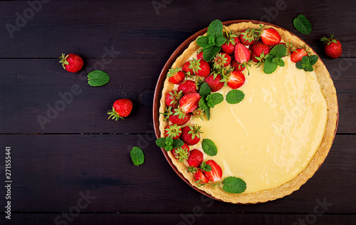 Valokuva Tart with strawberries and whipped cream decorated with mint leaves on dark background