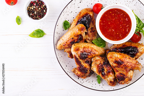 Baked chicken wings in the Asian style and tomatoes sauce on plate. Top view