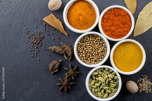 Foto op Canvas Kruiden Spices in little white bowls on black slate background - Indian spice - top view photo