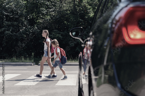 Low angle on car in front of children with backpacks walking through crosswalk t Fototapet