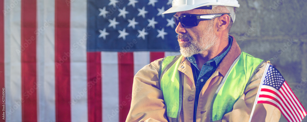 Fototapety, obrazy: American worker  builder looking sideways with stars and stripes flag in background, wide image, toned