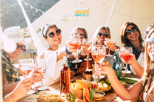 Foto op Aluminium Kruidenierswinkel Cheerful group of happy female people clinking and toasting together with friendship and happiness - young and adult women have fun eating - food and beverage celebration concept