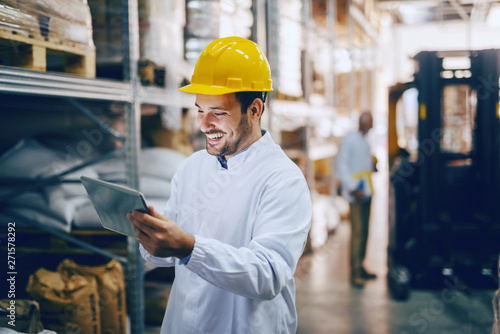 Young smiling Caucasian auditor in white uniform and with yellow helmet on head using tablet for checking on goods in warehouse Canvas Print