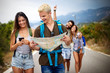 Adventure, travel, tourism and people concept - group of smiling friends with backpacks and map