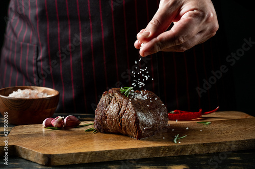 Garden Poster Steakhouse Chef hands cooking meat steak and adding salt and pepper on black copy space background for menu restaurant or recipe text.