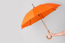 Female Hand With Umbrella On Light Background