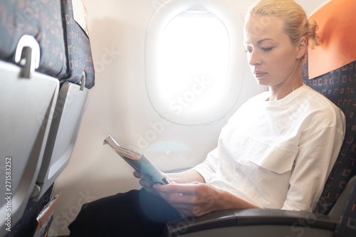 fototapeta na lodówkę Woman reading in flight magazine on airplane. Female traveler reading seated in passanger cabin. Sun shining trough airplane window.