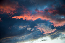A Stormy Sky With A Bright Red Glow. Colorful Image Of Dramatic Cloudscape. Amazing Clouds Of Pink, White, Gray Color On The Background Of The Evening Dark Sky After Sunset.