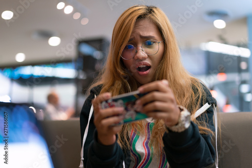 Photo  Ethnic Asian female with a shocked expression while playing mobile app games - Y