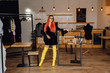 Fancy Dressed Woman Designer in Fashion Showroom. Attractive Female Redhead Model Wearing Stylish Black Dress and Yellow Boots Looking at Camera. Brand New Clothes Collection at Cozy Boutique