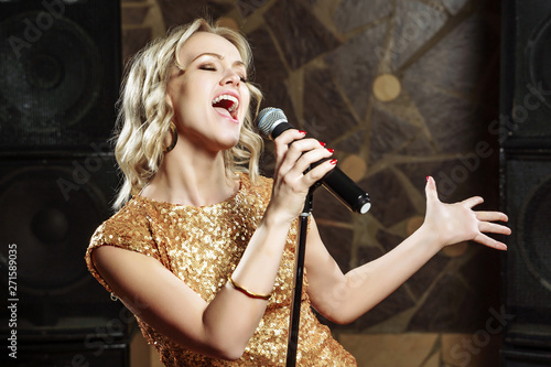Beautiful young woman singing with the microphone Wallpaper Mural
