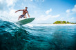 canvas print picture Young surfer with lean muscular body rides the tropical wave