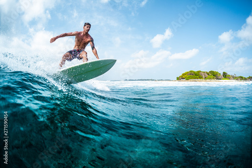 Fototapeta  Young surfer with lean muscular body rides the tropical wave