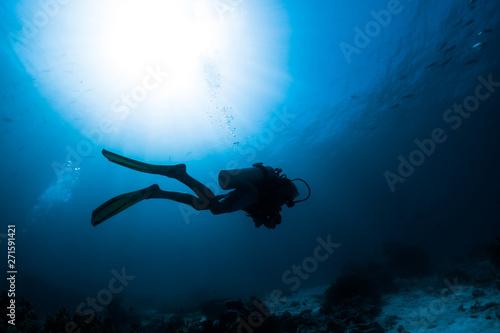 Valokuva  Silhouette of the scuba diver swimming alone in the depth