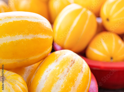 Photo  Delicious korean stripe yellow melon fruit food in red plastic basket at tradition market afternoon, Seoul, South Korea, harvest concept, close up