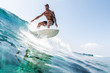 canvas print picture Young hispanic man surfs the glassy ocean wave at sunny day