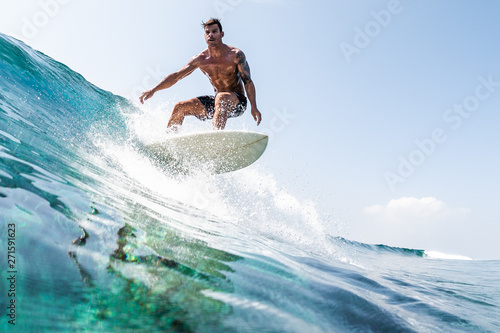 Young hispanic man surfs the glassy ocean wave at sunny day Wallpaper Mural