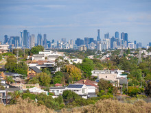 View Of Melbourne's Residential Houses In Suburb With Skyscrapers In City At Background.