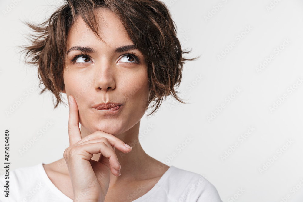 Fototapeta Beautiful young pretty thinking thoughtful woman posing isolated over white wall background.