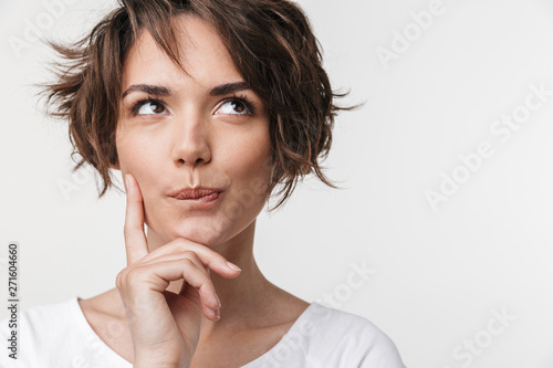 Obraz Beautiful young pretty thinking thoughtful woman posing isolated over white wall background. - fototapety do salonu
