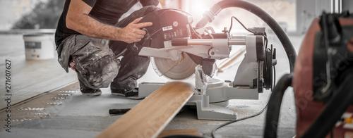 Fotografia Handwerker schneidet Holzdiele mit der Kappsäge auf der Baustelle und die Späne