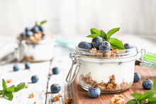 Healthy Breakfast Of Blueberry Parfaits Made With Fresh Fruit, Greek Yogurt, Granola And Mint Leaves Over A Rustic White Table. Selective Focus On Glass Jar In Front With Blurred Background.