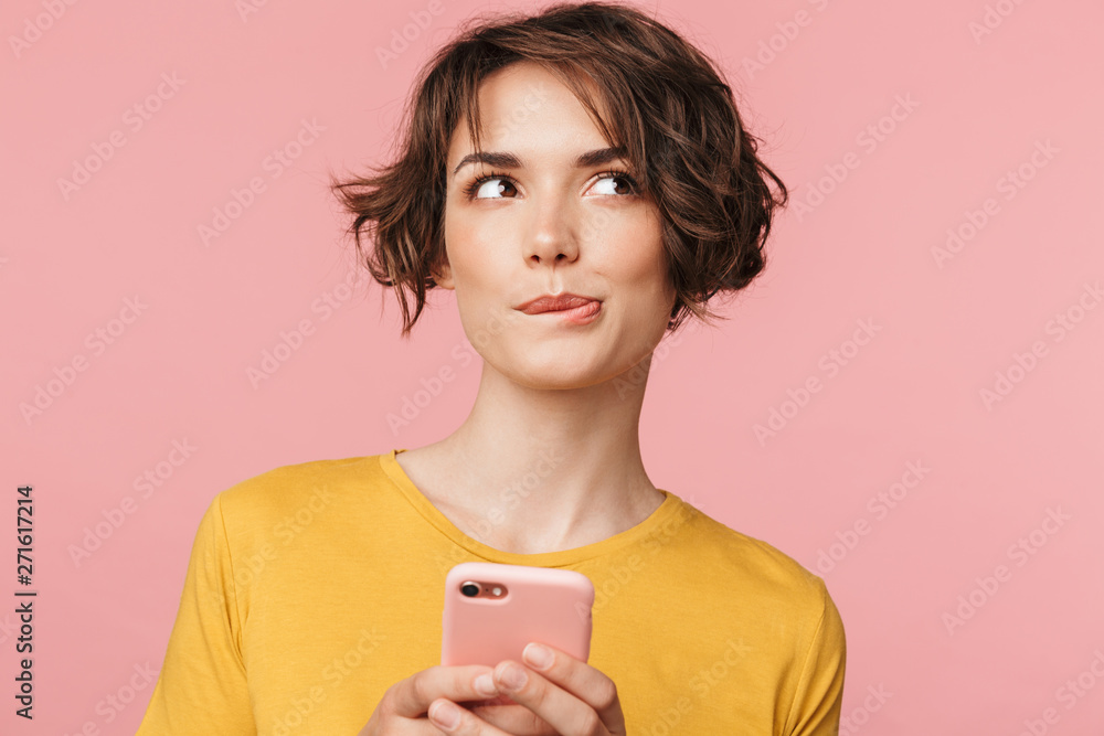 Fototapety, obrazy: Thinking dreaming young beautiful woman posing isolated over pink wall background using mobile phone.