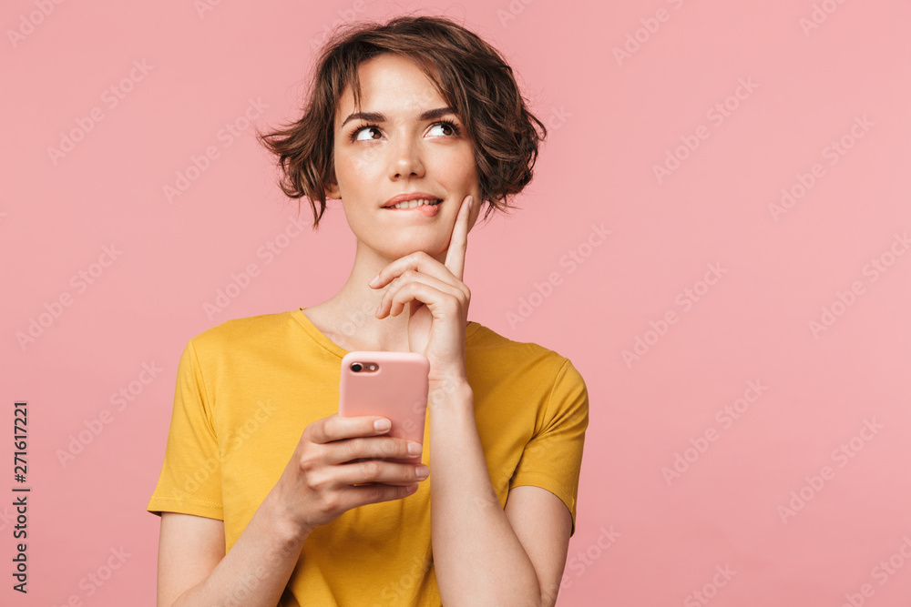 Fototapety, obrazy: Dreaming young beautiful woman posing isolated over pink wall background using mobile phone.