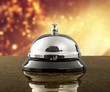 Vintage hotel reception service desk bell on wooden table with abstract background