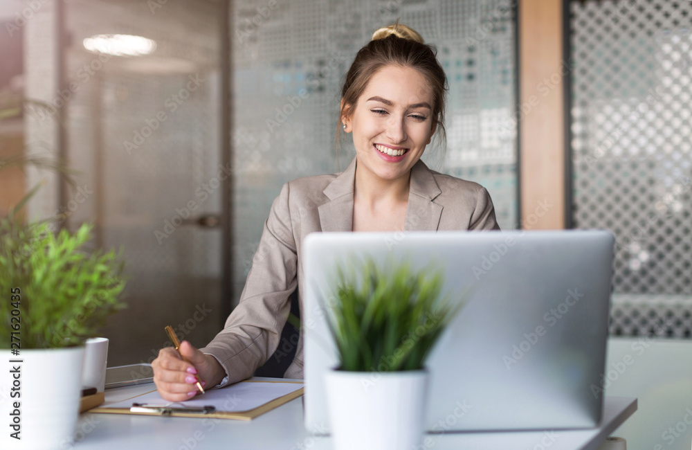 Fototapeta Young business woman working on laptop in office