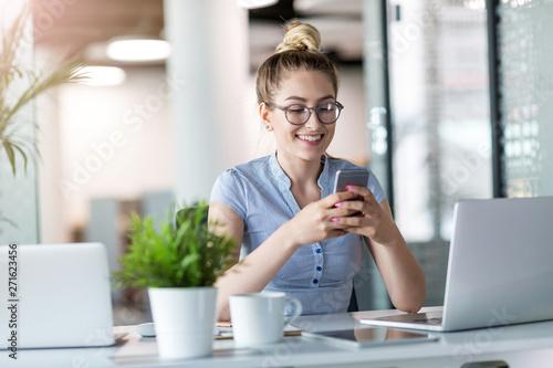 Fototapeta Business woman using smartphone in office obraz na płótnie