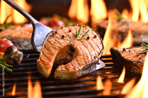Fototapeta Grilled salmon fish with various vegetables on the flaming grill obraz