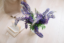 Bouquet Of Purple Lupins In A Vase In The Cozy Home Interior. Summer Floral Concept. Top View Summer Floral Blogger Composition.