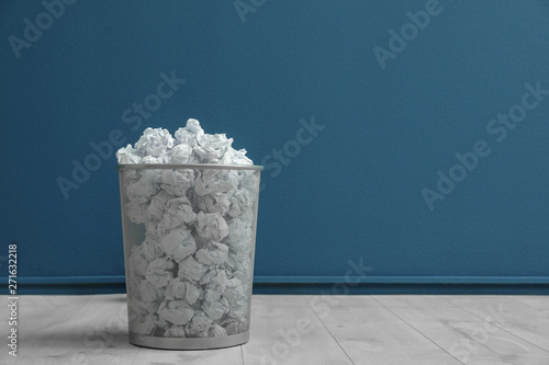 Fototapety, obrazy: Metal bin with crumpled paper on floor against color wall. Space for text