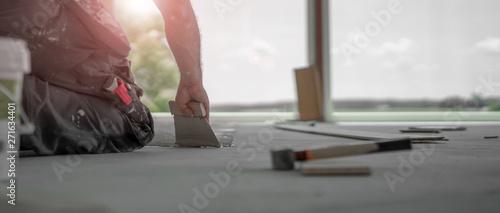 Fototapeta Handwerker verteilt den Parkettkleber mit der Kleberspachtel auf dem frischen Estrich beim Parkett legen obraz