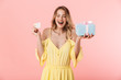 Leinwanddruck Bild - Excited emotional happy young blonde woman posing isolated over pink wall background holding present gift box and credit card.