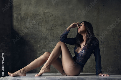 Fashion and portrait photography background, a beautiful female model is wearing lace body suit and posing for portrait photography.