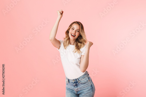 Foto Happy young blonde woman posing isolated over pink wall background make winner gesture