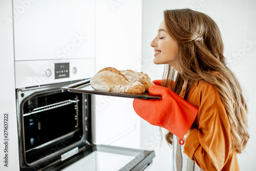 Photo Stands Bread Beautiful young woman baking bread in the oven at the modern white kitchen at home