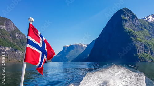 Wall Murals Northern Europe Norwegian flag hanging on the railing of the ship and waving above the water.The motor of the ship makes the water wavy and foamy. Tall, lush green mountains surrounding the fjord. Clear blue sky.