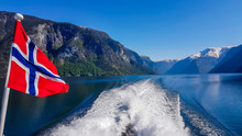 Norwegian Flag Hanging On  The Railing Of The Ship And Waving Above The Water.The Motor Of The Ship Makes The Water Wavy And Foamy. Tall, Lush Green Mountains Surrounding The Fjord. Clear Blue Sky.