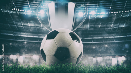Fotografia Close up of a soccer ball with trophy in the center of the stadium illuminated b