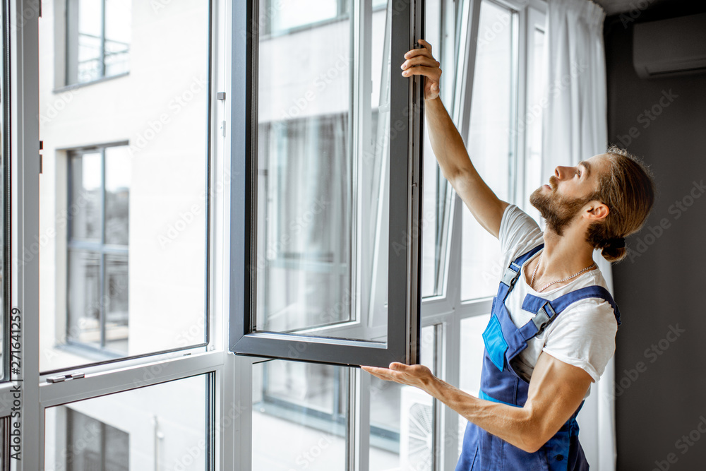 Fototapeta Workman in overalls installing or adjusting plastic windows in the living room at home