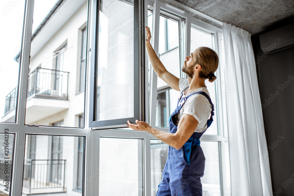 Fototapety, obrazy: Workman in overalls installing or adjusting plastic windows in the living room at home