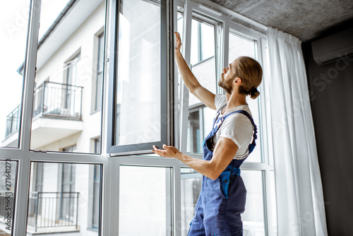 Workman in overalls installing or adjusting plastic windows in the living room at home