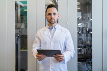Portrait Of Man With Tablet Wearing Lab Coat In Modern Factory
